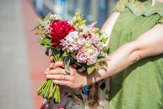 Schöne frau im weißen mantel mit roten rosen in der hand