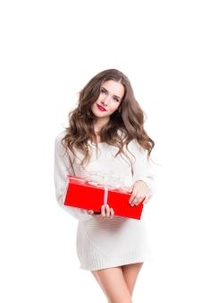 Schöne frau im weißen pullover, der rote box mit geschenk hält, lokalisiert
