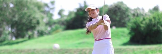 Schöne frau im weißen rock, in der kappe und im rosa t-shirt spielen golf auf grünem rasen.