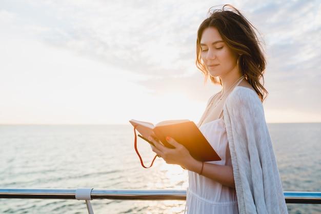 Schöne frau im weißen sommerkleid, das durch das meer auf sonnenaufgang mit tagebuchbuch in der romantischen stimmung denkt und notizen macht