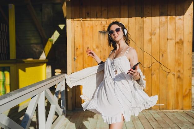 Schöne frau im weißen sommerkleid, das musik auf kopfhörern hört, die tanzen und spaß haben, smartphone halten, sommerferienart