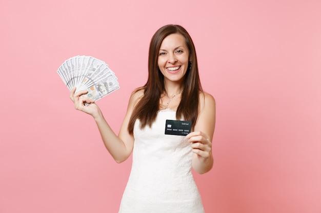 Schöne frau im weißen spitzenkleid, das bündel viele dollar bargeld und kreditkarte hält