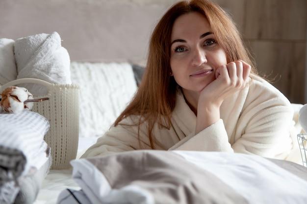 Schöne frau im winter dicke warme robe sitzt und ordentlich klappbettwäsche und weiße badetücher. saubere wäsche organisieren und sortieren. textil aus bio- und naturbaumwolle. herstellung.