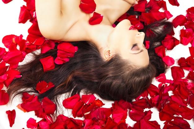 Schöne frau in blütenblättern von roten rosen über weiß
