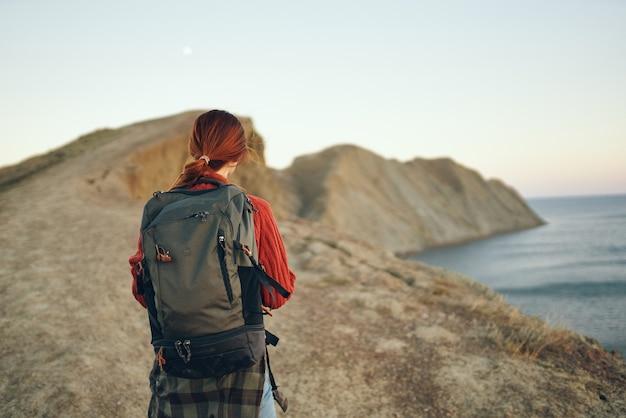 Schöne frau in den bergen in der natur mit einem rucksack auf dem rücken nahe dem meer