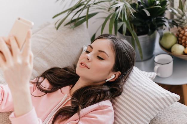 Schöne frau in den drahtlosen kopfhörern, die musik hören, auf sofa liegend und im smartphone plaudern