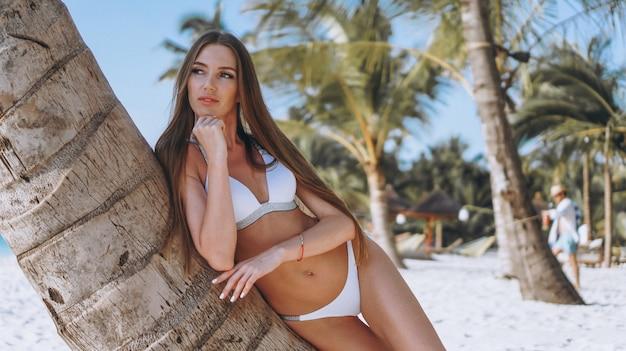 Schöne frau in der badeabnutzung durch den ozean durch die palme