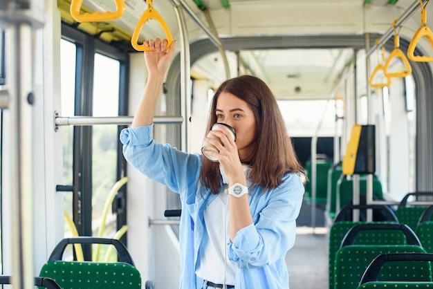 Schöne frau in der blauen scheiße trinkt kaffee, während im öffentlichen verkehr reitend.