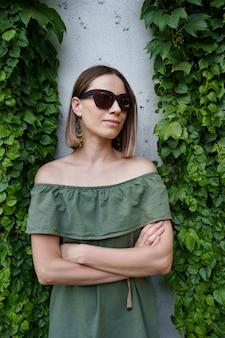 Schöne frau in der braunen sonnenbrille, die neben pflanzen aufwirft. foto im freien der herrlichen jungen dame in der grünen kleidung, die mit gekreuzten händen zwischen grünen blättern aufwirft
