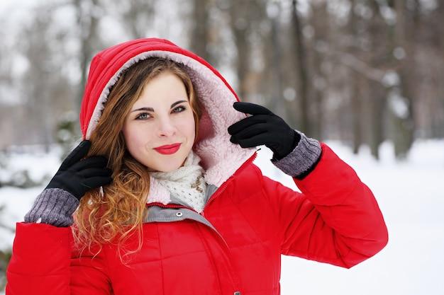 Schöne frau in der haube auf einem schneebedeckten feld im winter