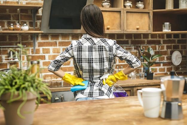 Schöne frau in der küche, die staub mit einem spray und einem staubtuch abwischt, während sie ihr haus reinigt.