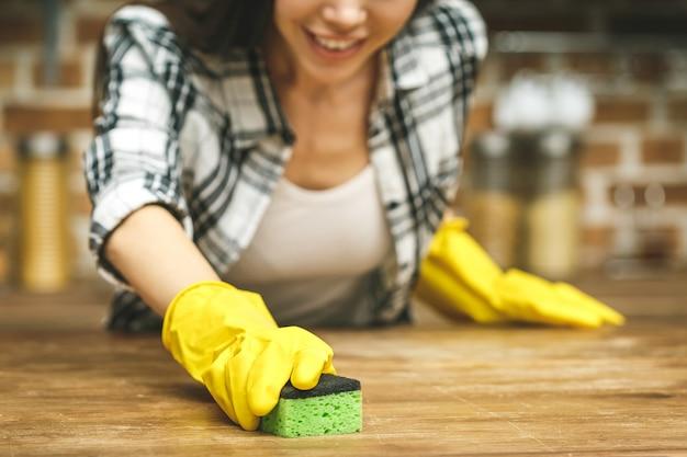 Schöne frau in der küche lächelt und wischt staub mit einem spray und einem staubtuch ab, während sie ihr haus putzt, nahaufnahme