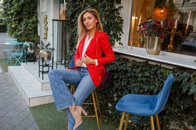 Schöne frau in der roten jacke, die im straßencafé ruht