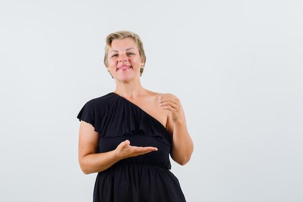 Schöne frau in der schwarzen bluse, die offene handfläche beiseite spreizend etwas zeigt und erfreut aussieht