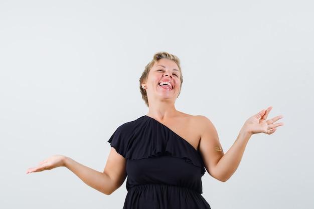 Schöne frau in der schwarzen bluse, die offene handfläche beiseite spreizend etwas zeigt und lustig aussieht