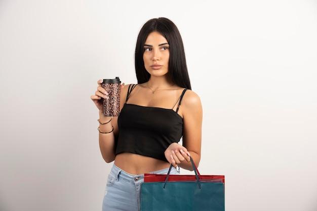 Schöne frau in der schwarzen spitze, die taschen und kaffee hält. hochwertiges foto