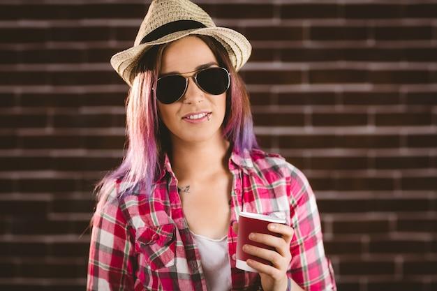 Schöne frau in der sonnenbrille, die kaffeetasse hält