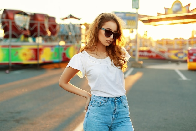 Schöne frau in der sonnenbrille und im weißen t-shirt im park bei sonnenuntergang.