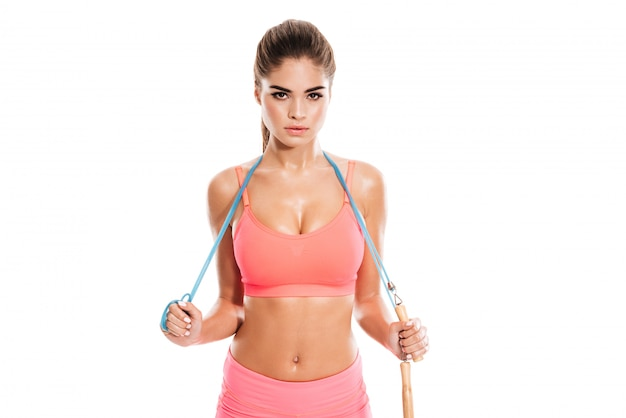 Schöne frau in der sportkleidung, die mit springseil steht