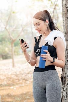 Schöne frau in der sportkleidung, die wasserflasche hält und smartphone nach dem laufen verwendet.