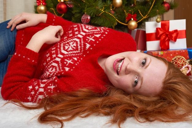 Schöne frau in der weihnachtsdekoration, die nahe weihnachtsbaum aufwirft