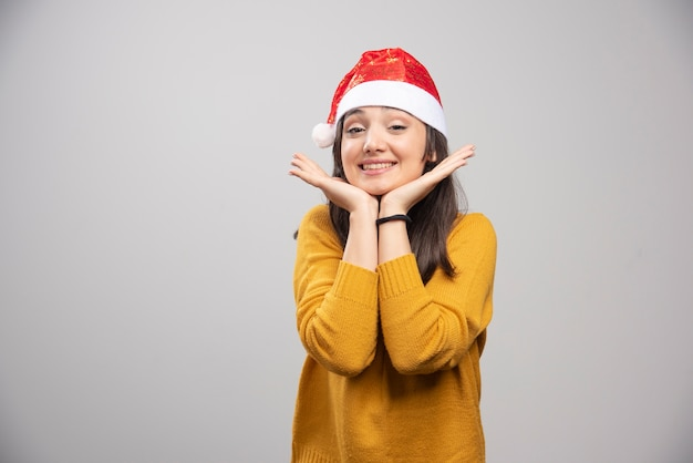 Schöne frau in der weihnachtsmütze, die glücklich auf grauer wand fühlt.