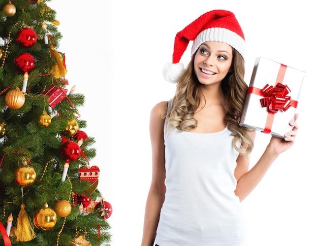 Schöne frau in der weihnachtsmütze mit geschenk nahe dem weihnachtsbaum