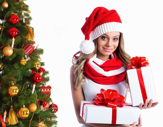 Schöne frau in der weihnachtsmütze mit geschenken nahe dem weihnachtsbaum