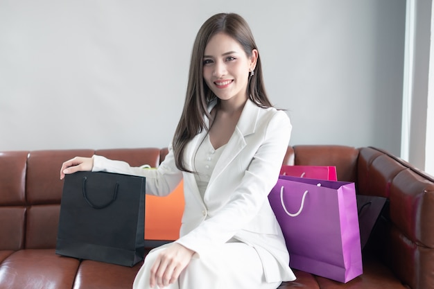 Schöne frau in der weißen klage ist glücklich, nachdem sie eingekauft hat.