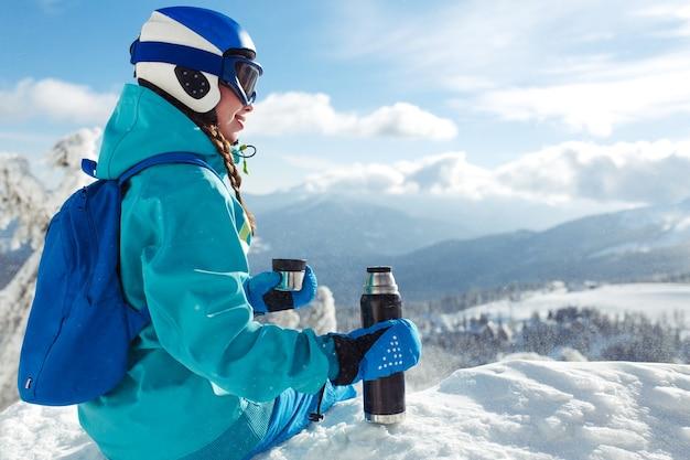 Schöne frau in der winterkleidung, die tee in den bergen trinkt. konzept von reisen, freizeit, freiheit, sport.