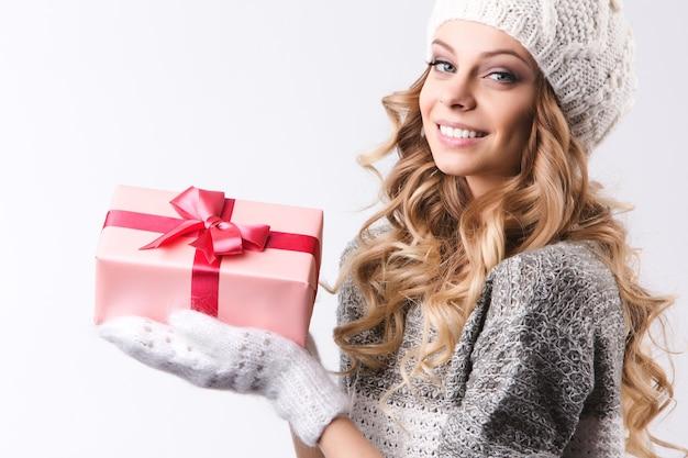 Schöne frau in der winterkleidung mit weihnachtsgeschenken auf weißem hintergrund.