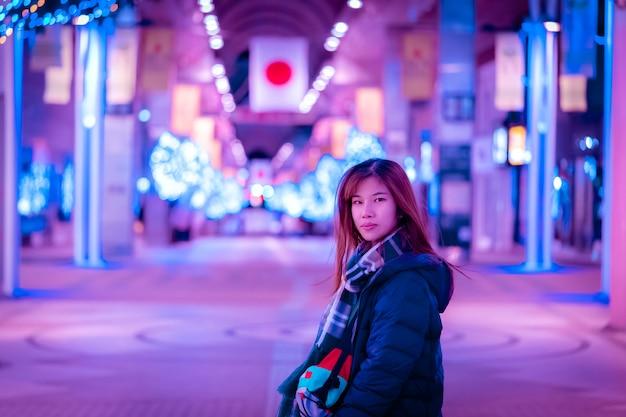 Schöne frau in der wintermodekleidung in der japanstraße bei nacht.