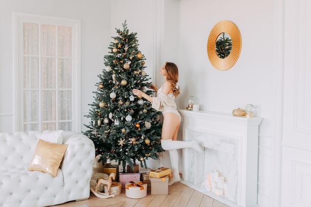 Schöne frau in dessous und leggings schmückt den weihnachtsbaum in der nähe des kamins zu hause