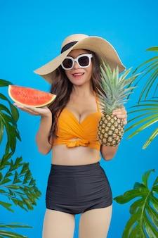 Schöne frau in einem badeanzug, der ananas und wassermelone auf blau hält