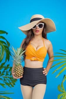 Schöne frau in einem badeanzug, der eine ananas auf blau anhält