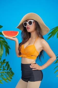 Schöne frau in einem badeanzug, der eine wassermelone auf blau anhält