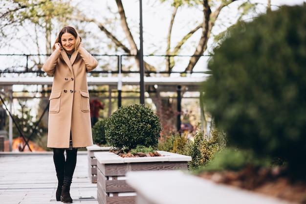 Schöne frau in einem beige mantel draußen im park