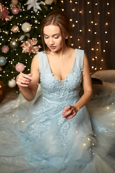 Schöne frau in einem blauen abendkleid auf dem hintergrund eines weihnachtsbaums und girlanden