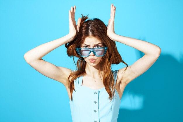 Schöne frau in einem blauen hintergrundlebensstil des kleides und der brille