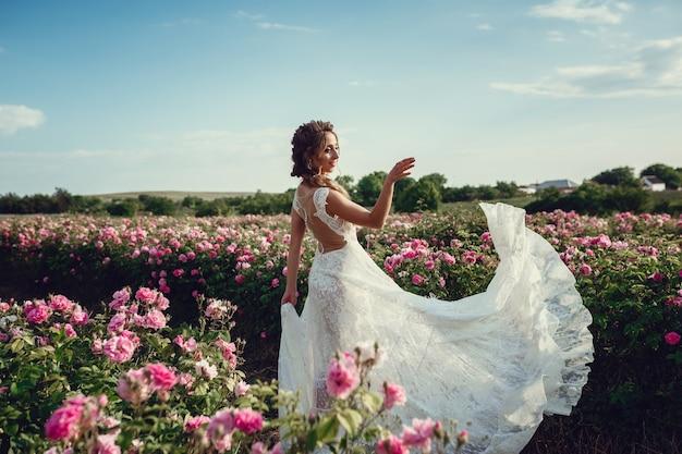 Schöne frau in einem blumenpark, gartenrosen. make-up, haare, ein rosenkranz. langes hochzeitskleid. frau im boho-stil