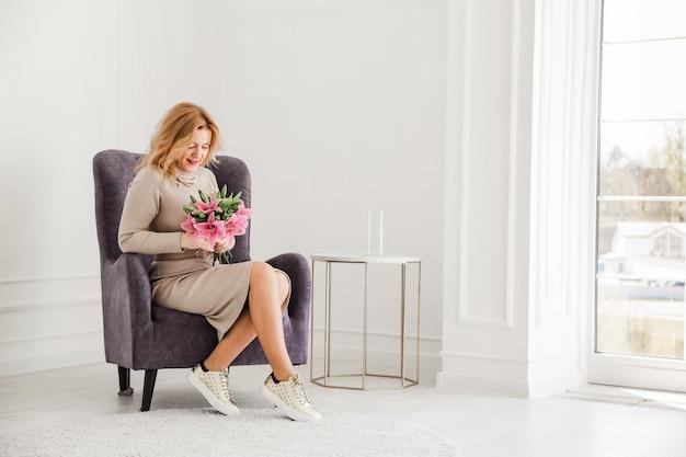 Schöne frau in einem engen kleid und turnschuhen sitzt auf einem stuhl mit einem blumenstrauß und einem lächeln.