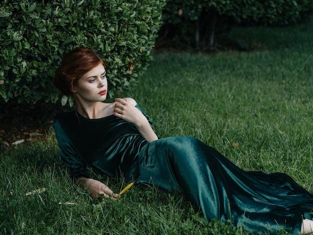 Schöne frau in einem grünen kleid liegt auf dem luxusmodell der grünen buschgrasnatur.