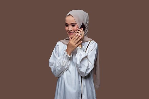 Schöne frau in einem hijab, die auf ihrem handy mit lächelnausdruck auf ihrem gesicht flüstert Premium Fotos