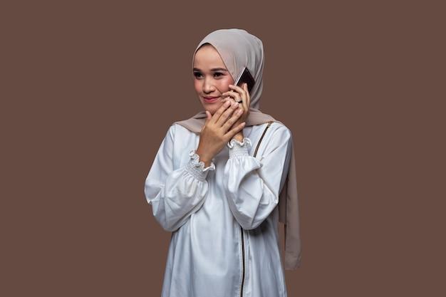 Schöne frau in einem hijab, die auf ihrem handy mit lächelnausdruck auf ihrem gesicht flüstert