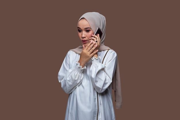 Schöne frau in einem hijab, die mit erstauntem gesichtsausdruck auf ihrem handy flüstert