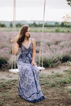 Schöne frau in einem langen kleid sitzt auf einer schaukel in einem lavendelfeld bei sonnenuntergang.