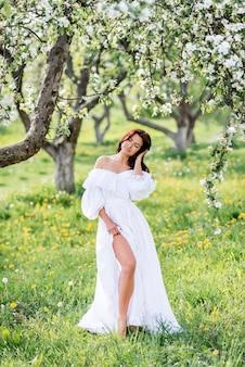 Schöne frau in einem langen weißen kleid mit einem schlitz auf ihrem bein in einem blühenden garten. ein mädchen in einem frühlingsgarten im gras ..
