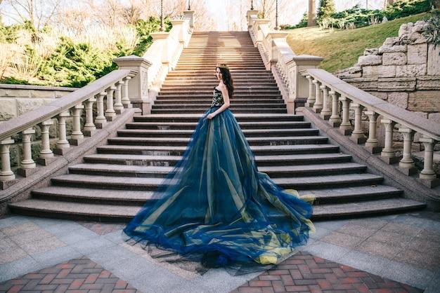 Schöne frau in einem luxuriösen blauen kleid mit einem langen zug