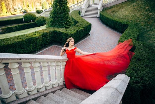Schöne frau in einem luxuriösen roten kleid mit einem langen zug