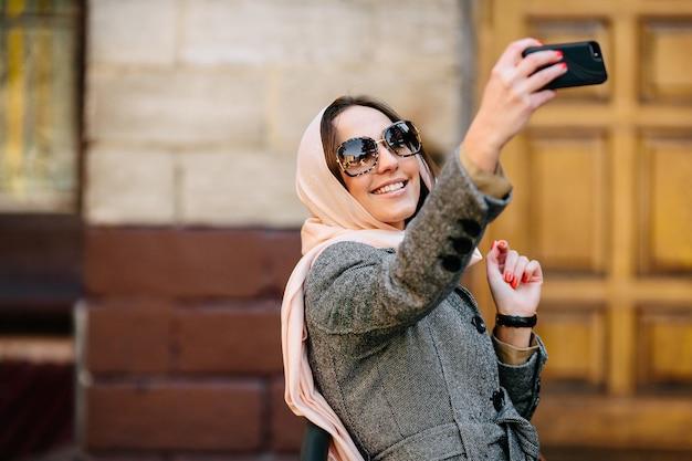 Schöne frau in einem mantel auf der straße macht selfie